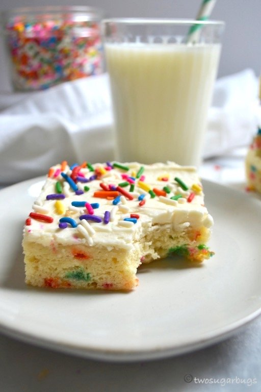 sugar cookie bar on a plate with a glass of milk in the background