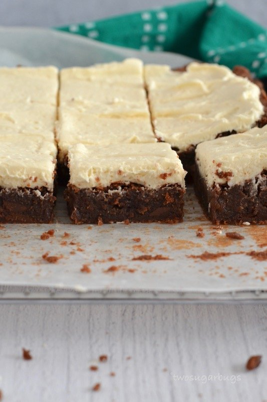Fudgy Irish Cream Brownies topped with a fluffy Irish cream buttercream. Perfect for St. Patrick's Day or honestly anytime! #twosugarbugs #irishcreambrownies #brownielove #bestbrownie