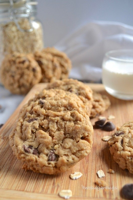 cookies on a cutting board with a cup of milk in the background