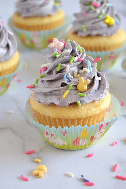 up close photo of lemon cupcake with blueberry buttercream