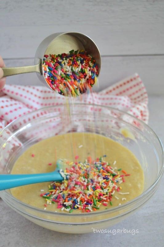 Action shot of sprinkles going into batter bowl