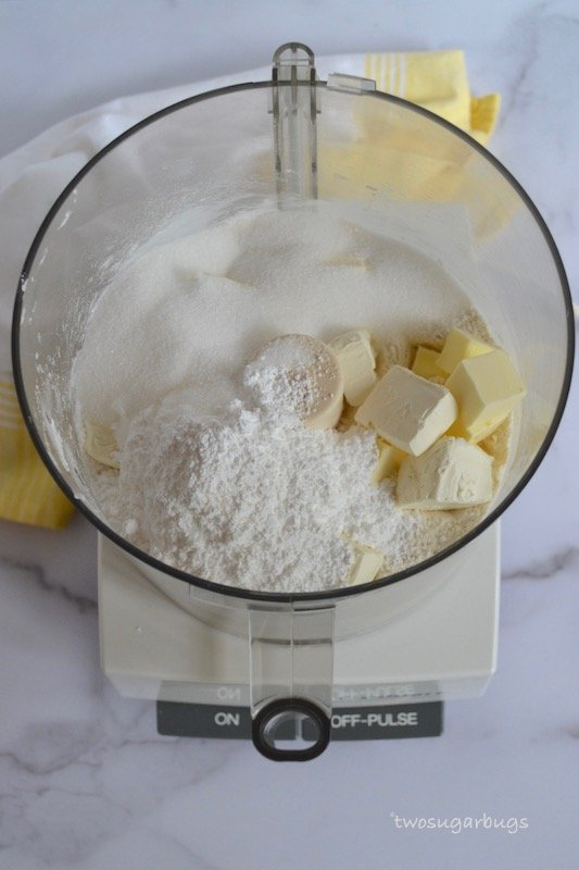 Sugar and butter on top of flour mixture in a food processor