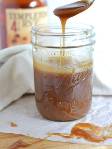 Mason jar of whiskey vanilla caramel sauce with a spoon dripping sauce back into the jar