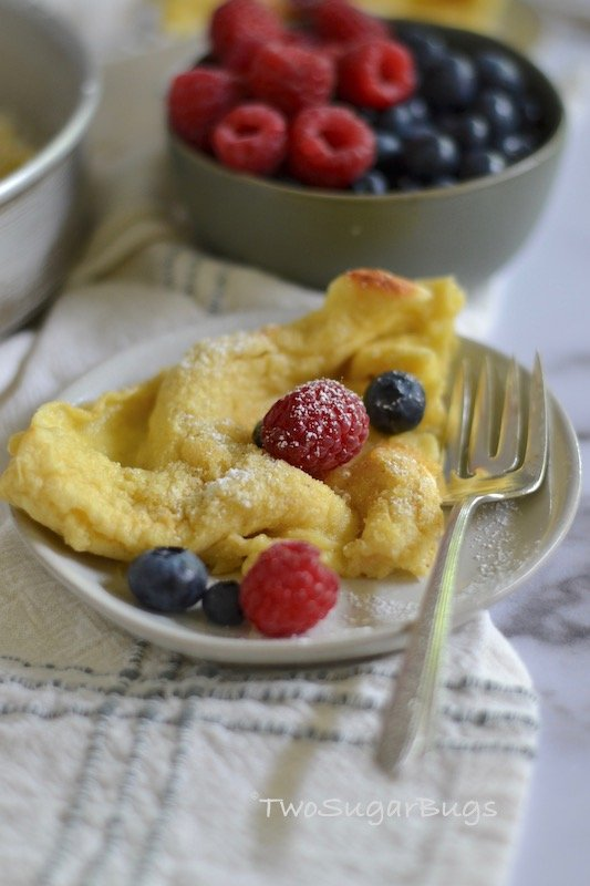 Dutch Baby on a plate with fresh berries in the background