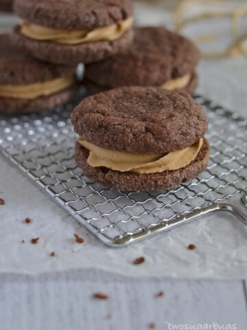 Chocolate Biscoff sandwich cookies on a wire rack.