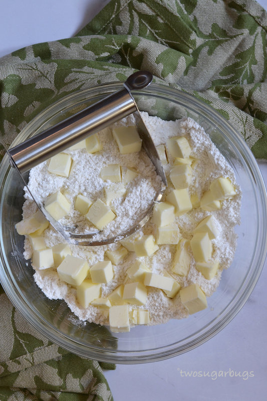 Bowl with flour, butter and a pastry cutter.