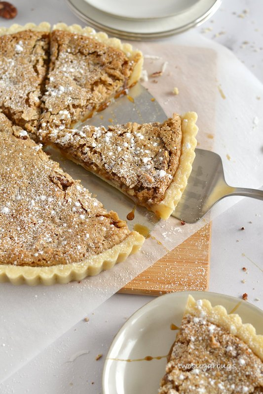 Coconut pecan tart with a cut slice on a cake server.
