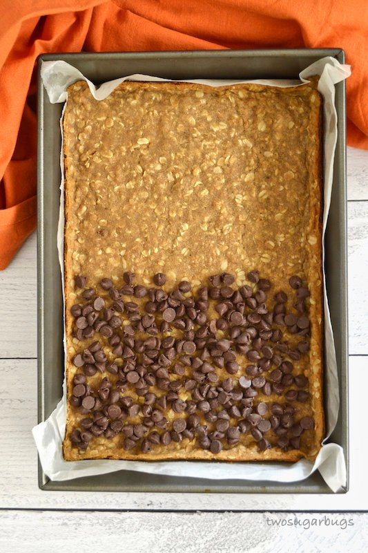 Baked oatmeal spice layer with chocolate chips over half.