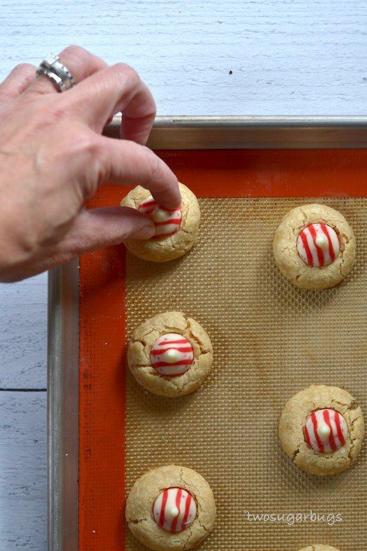hand placing a white chocolate candy cane kiss into a cookie