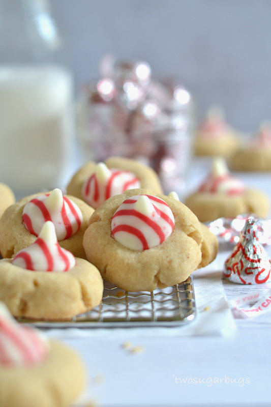 brown butter peppermint blossoms cookies on a cooling rack with kisses and milk in the background