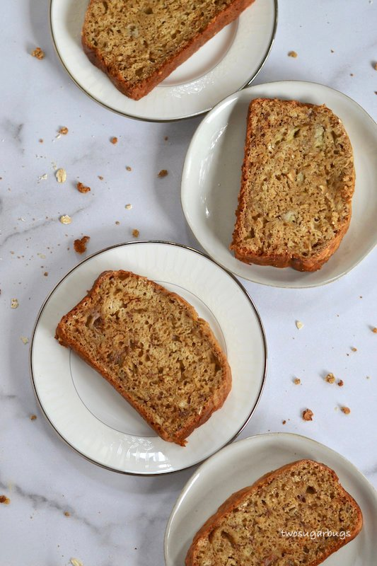 Four plates with slices of peanut butter oat banana bread