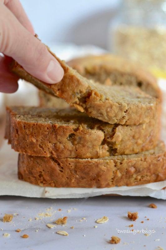A hand lifting a slice of banana bread