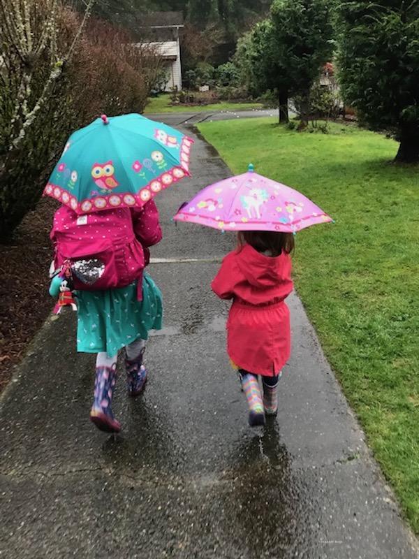 girls walking with umbrellas