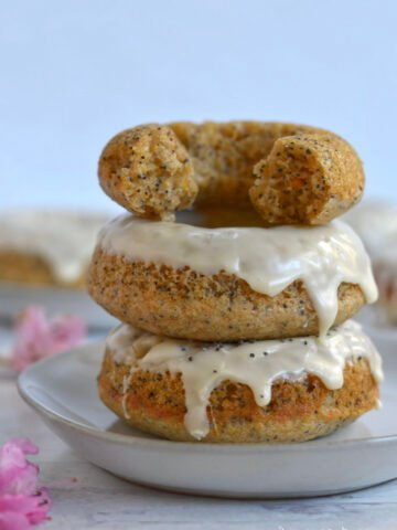 stack of three orange poppy seed donuts on a plate