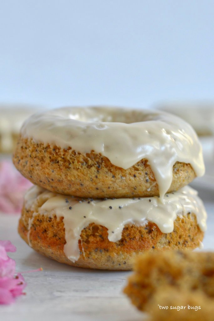 two orange poppy seed donuts stacked