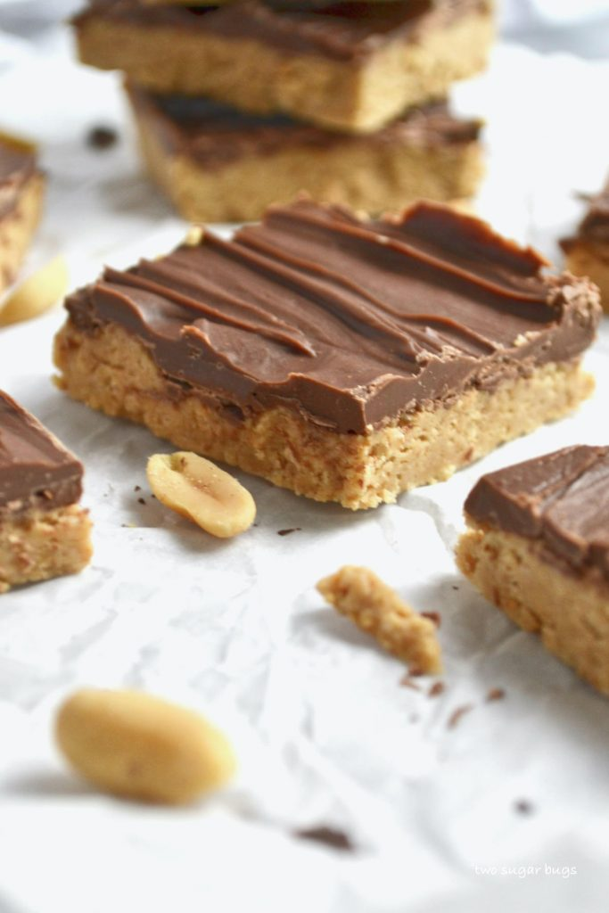 close up of peanut butter bars sitting on parchment paper