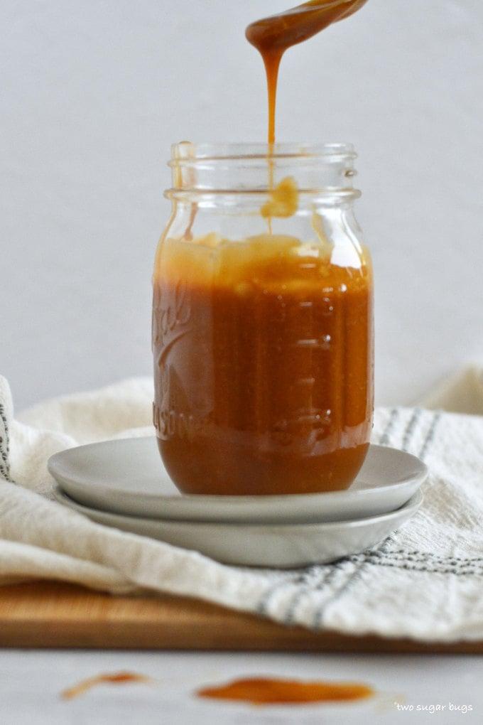a spoonful of caramel sauce dripping into a mason jar.