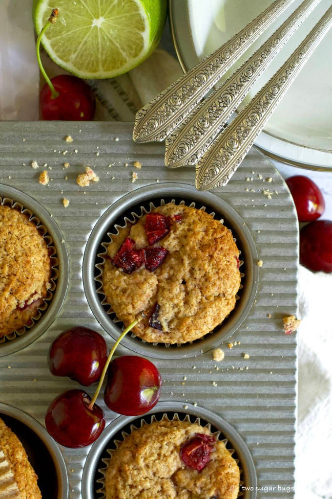 close up of muffins in a muffin pan with fresh cherries scattered about