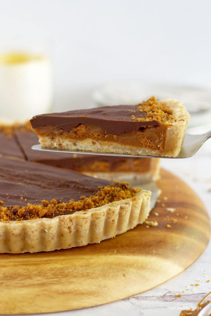 Slice of biscoff tart being lifted out of the tart pan