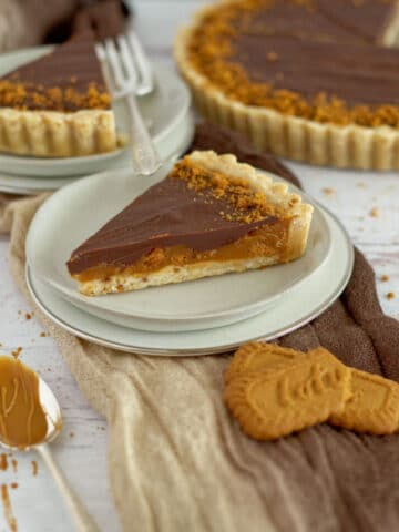 slice of biscoff caramel tart on three plates with full tart in the background