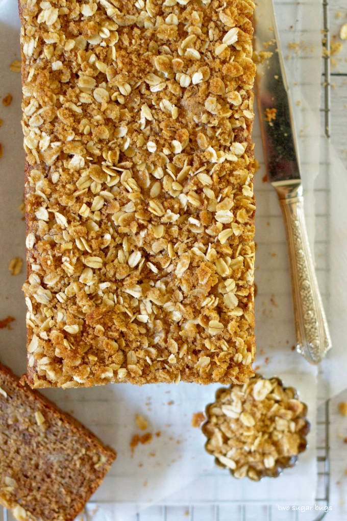apple cider oat streusel on top of banana bread sitting on a wire rack
