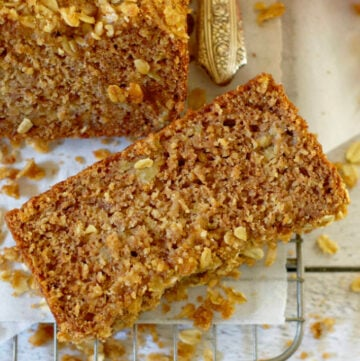 a slice of healthy, moist apple cider banana bread on a wire rack