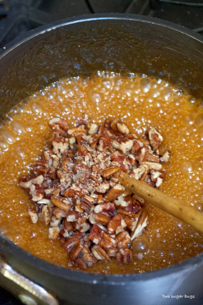 pecans being mixed into caramel sauce
