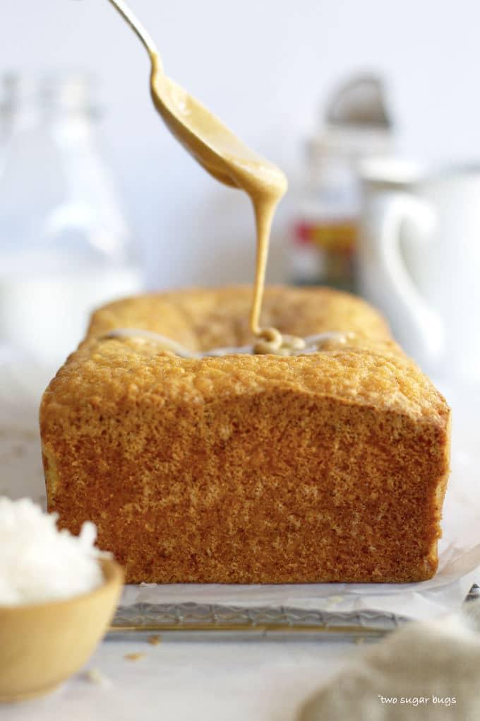 spoon drizzling glaze on kona coconut loaf cake