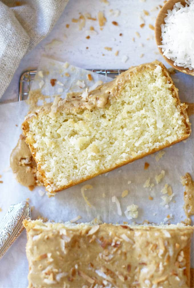 slice of coconut cake on parchment lined cooling rack
