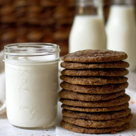 stack of cookies next to a glass of milk