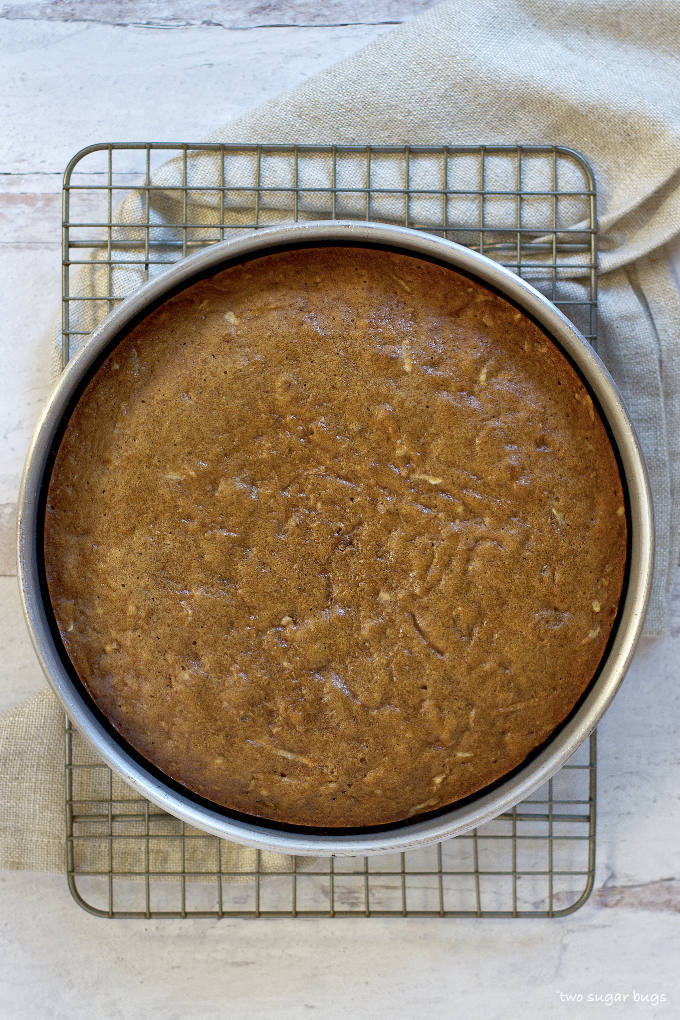 baked cake sitting in the pan on a cooling rack