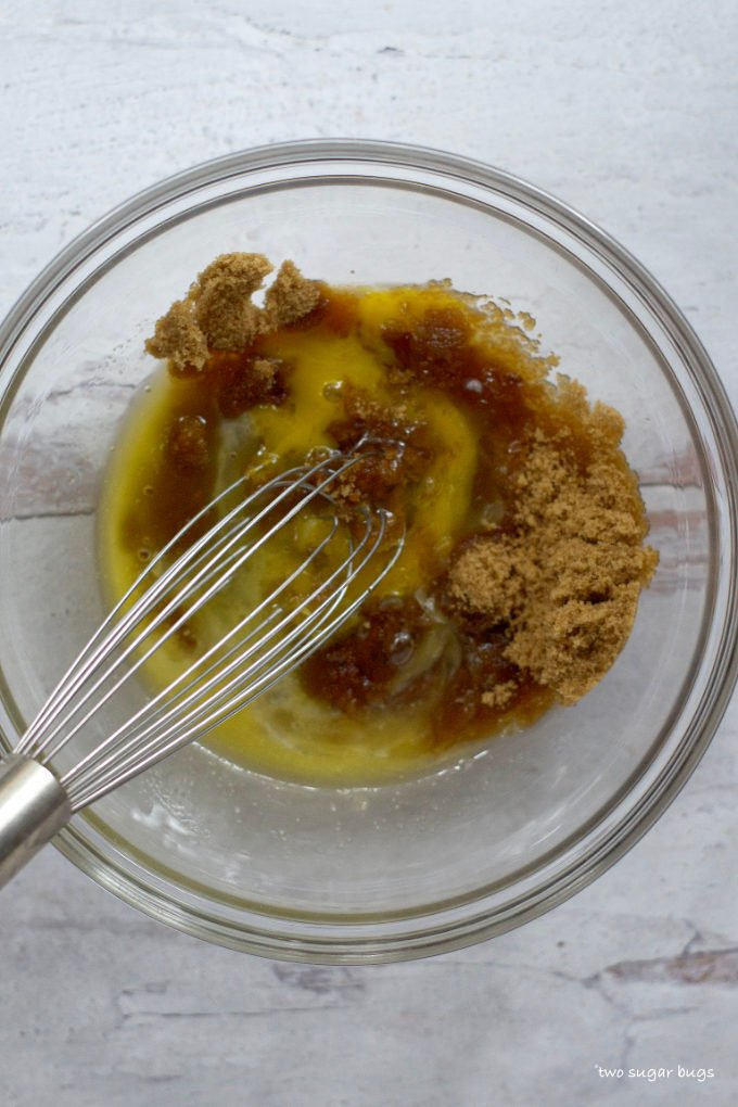 brown sugar, eggs and butter in a bowl with a whisk