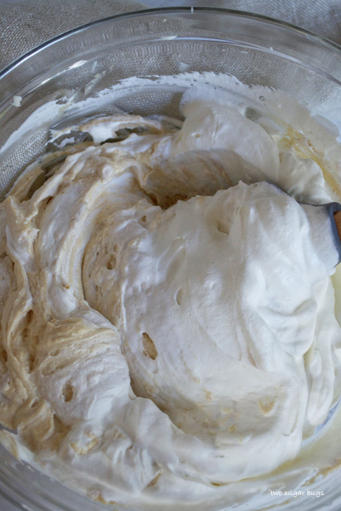 whipped cream being folded into peanut butter mixture with a spatula