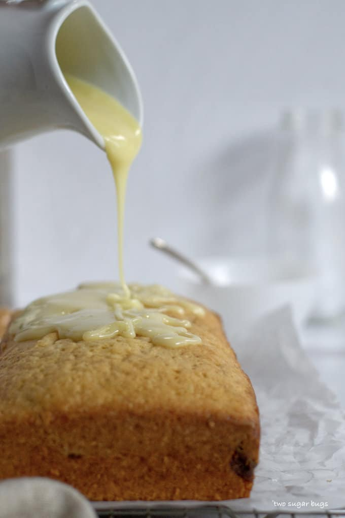 white chocolate glaze being poured on pound cake