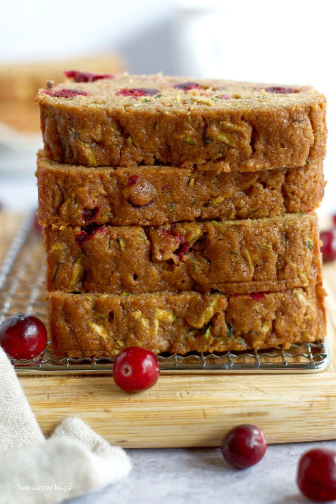 a stack of whole wheat cranberry zucchini bread slices on a cutting board