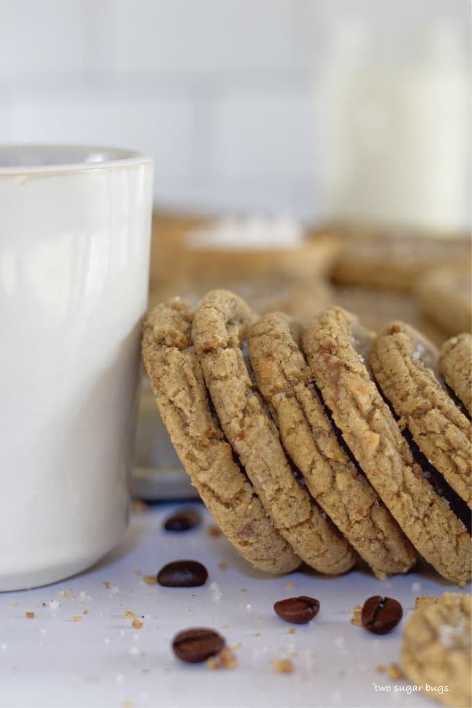 espresso brown butter toffee cookies leaning against a coffee cup