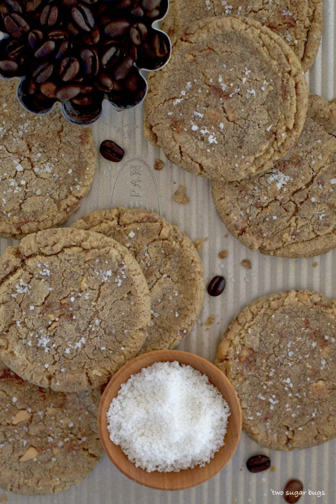 espresso brown butter toffee cookies on a baking sheet with salt and coffee beans
