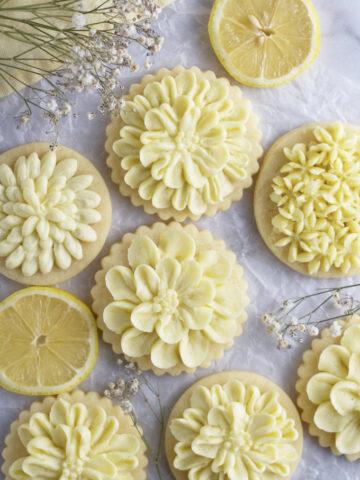 lemon cut out sugar cookies on parchment paper with lemon slices