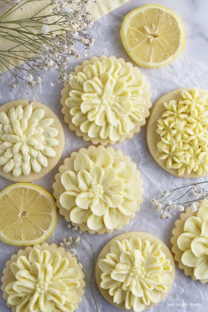 lemon cut out sugar cookies on parchment paper with lemon slices