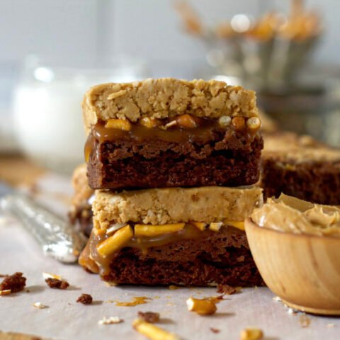 two brownies stacked on the counter with a glass of milk in the background