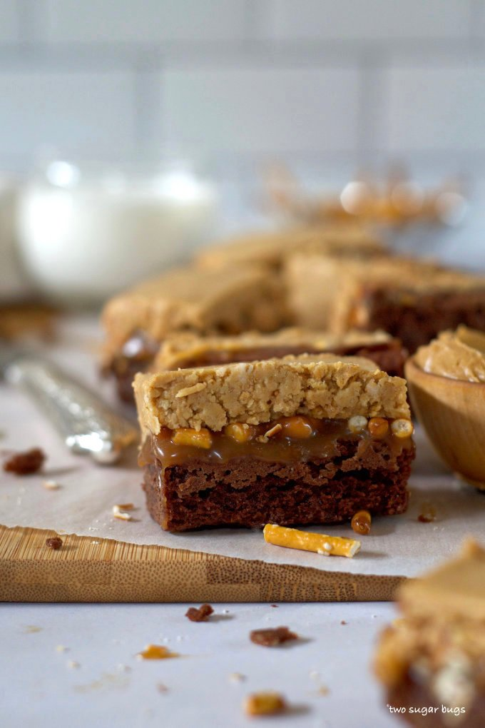 a single peanut butter caramel pretzel brownie on a parchment lined cutting board