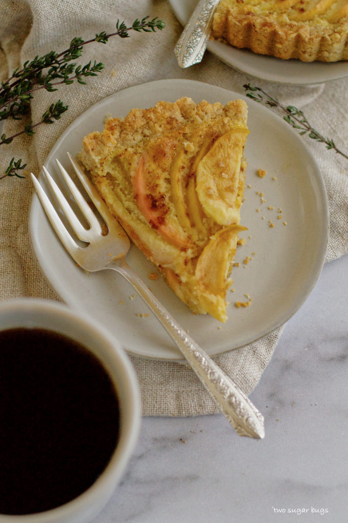 a slice of frangipane tart on a plate with a fork