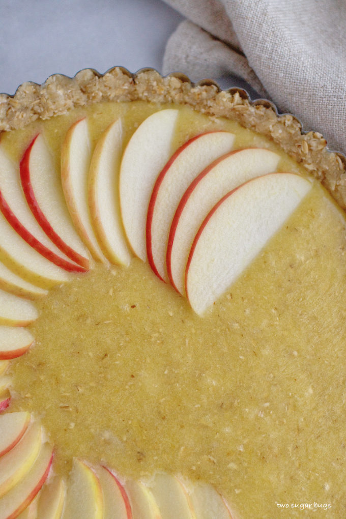 apple slices being fanned on top of Frangipane filling