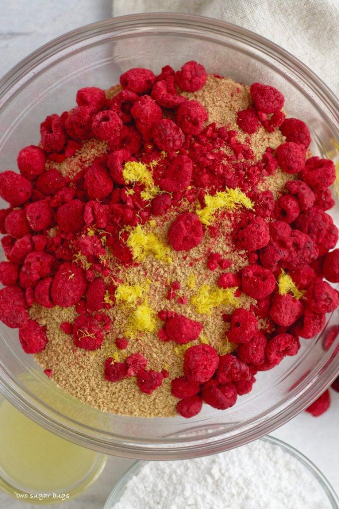 graham cracker crumbs, lemon zest and freeze dried raspberries in a bowl