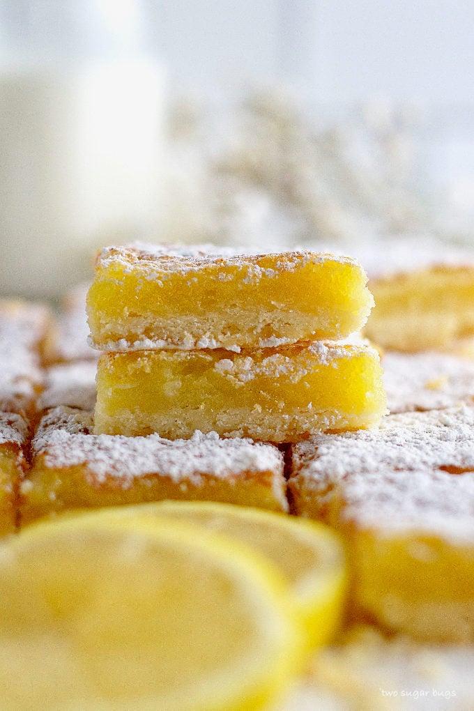 two lemon bars stacked on more lemon bars