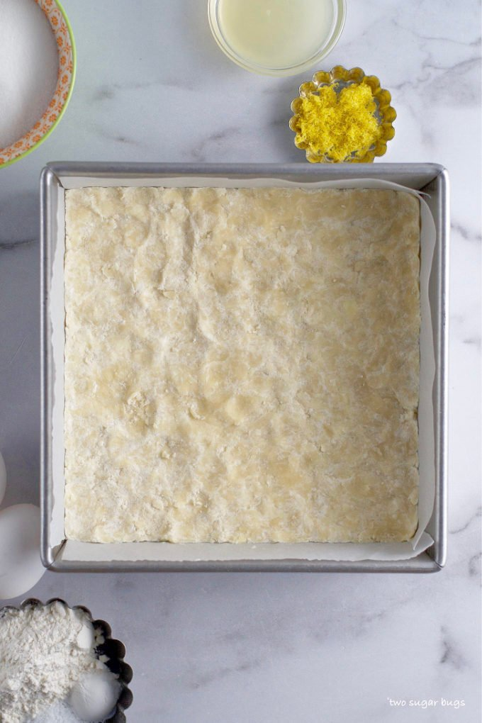 unbaked shortbread crust in parchment lined baking pan