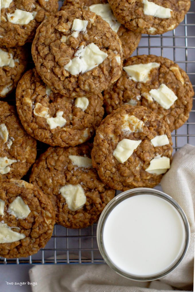 a pile of cookies on a cooling rack with a glass of milk