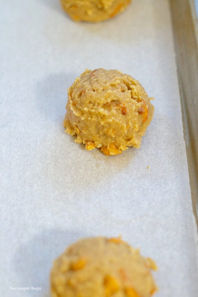 cookie dough scoops on a parchment lined baking sheet