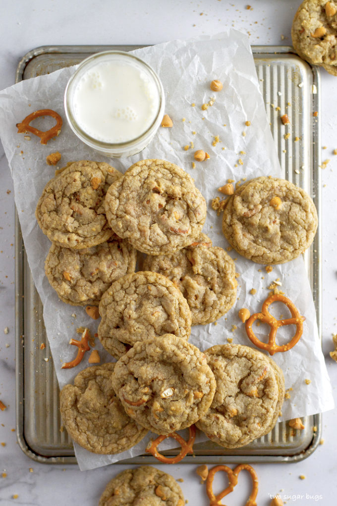 overhead look at butterscotch pretzel cookies and milk on parchment paper