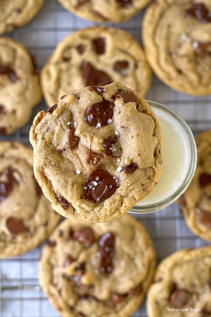chocolate chip cookie sitting on a glass of milk